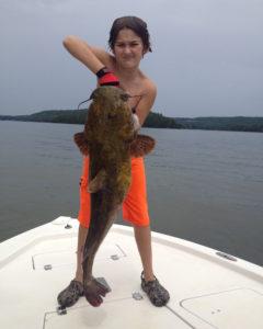 boy holding flathead catfish noodling on boat